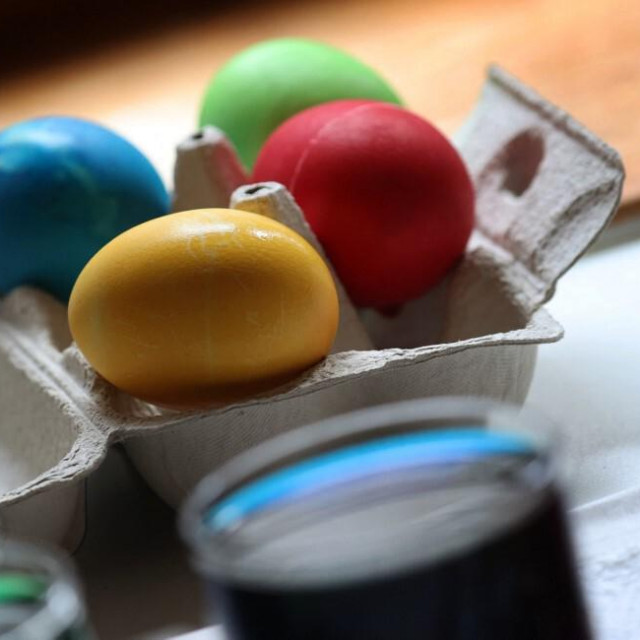 14 March 2021, Bavaria, Kempten: Colored hard boiled eggs lie behind jars of Easter egg paint. Photo: Karl-Josef Hildenbrand/dpa (Photo by KARL-JOSEF HILDENBRAND/DPA/dpa Picture-Alliance via AFP)