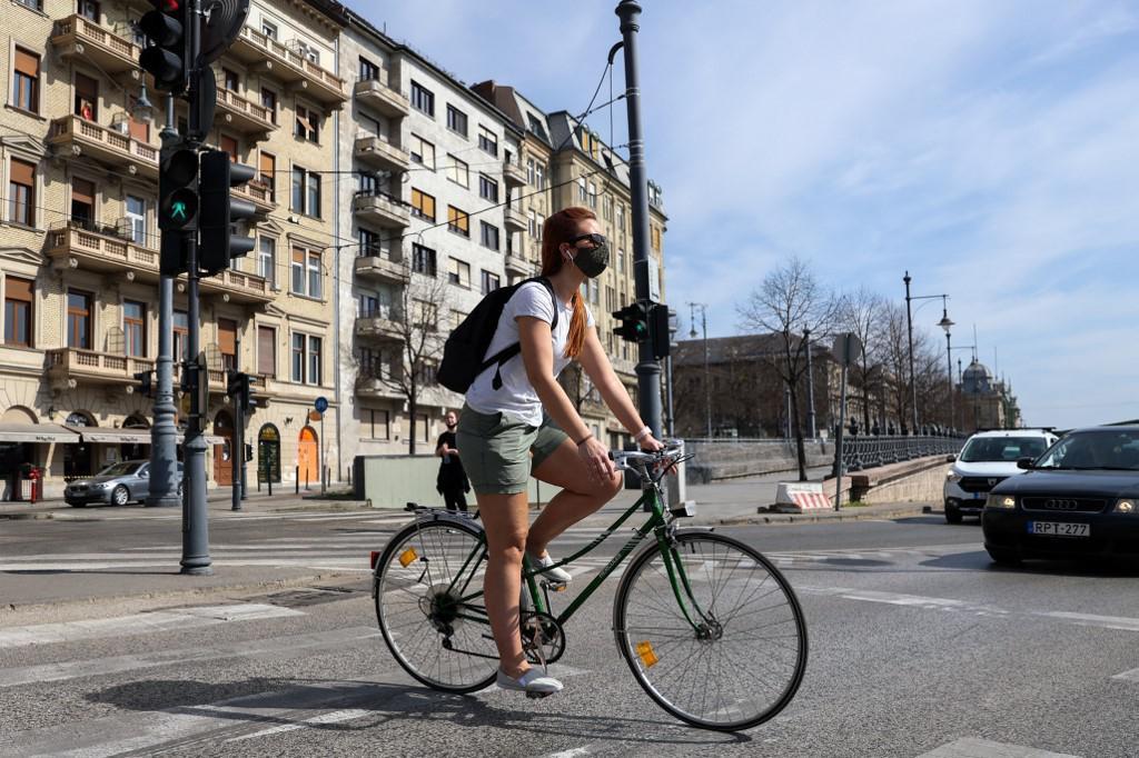 Mlada žena sa zaštitnom maskom vozi bicikl ulicama Budimpešte.