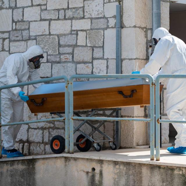 Djelatnici komunalne tvrtke Nasadi iznose lijes sa osobom preminulom od koronavirusa sa Covid odjela zadarske OB.<br />