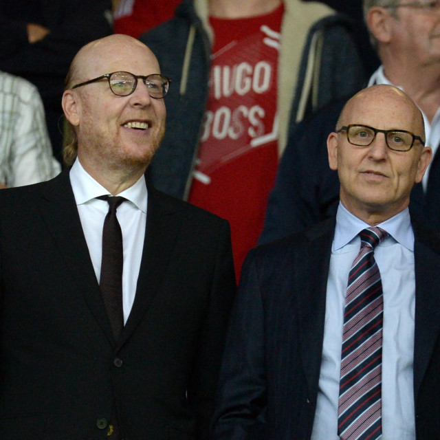 (FILES) In this file photo taken on August 19, 2016 Manchester United's US co-chairmen Joel Glazer (R) and Avram Glazer (L) attend the English Premier League football match between Manchester United and Southampton at Old Trafford in Manchester, north west England. - Twelve of Europe's most powerful clubs announced the launch of a breakaway European Super League on April 19, 2021 in a potentially seismic shift in the way football is run, but faced accusations of greed and cynicism. Six Premier League teams, Liverpool, Manchester United, Arsenal, Chelsea, Manchester City and Tottenham are involved, alongside Real Madrid, Barcelona, Atletico Madrid, Juventus, Inter Milan and AC Milan. Real Madrid chief Florentino Perez, who was announced as the first ESL president, said the breakaway reflected the big clubs' wishes. (Photo by Oli SCARFF/AFP)/RESTRICTED TO EDITORIAL USE. No use with unauthorized audio, video, data, fixture lists, club/league logos or 'live' services. Online in-match use limited to 75 images, no video emulation. No use in betting, games or single club/league/player publications./