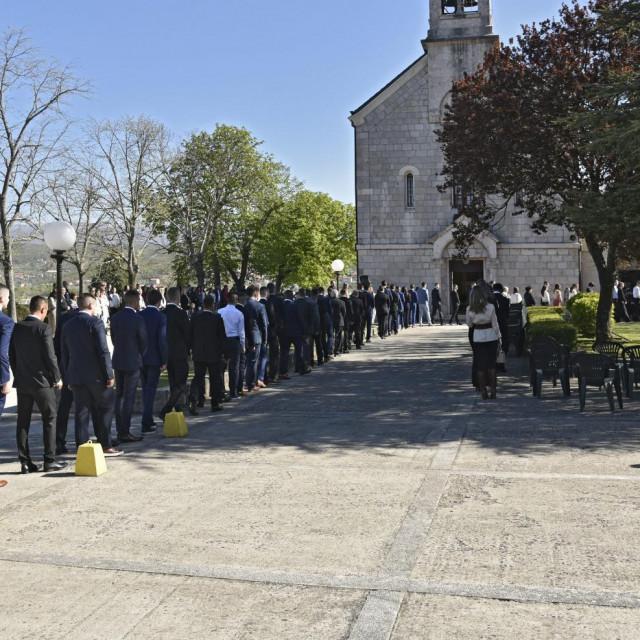 U mjestu Otok kod Sinja u župnoj crkvi sv. Luke krizmanici u koloni ulaze u prostor za misu ispred crkve