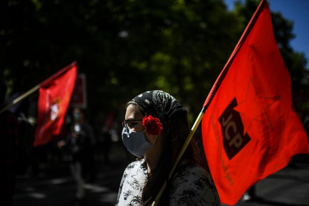 Žena koja nosi masku za lice drži zastavu i na glavi nosi crveni karanfil u znak obilježavanja godišnjice portugalske revolucije Crvenih karanfila
