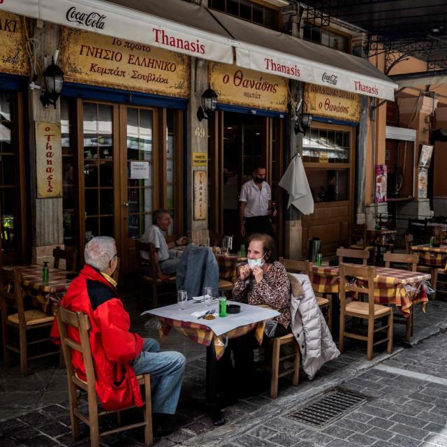 Ljudi sjede na terasi restorana na trgu Monastiraki u Ateni 3. svibnja 2021., dok se restorani i kafići u Grčkoj otvaraju nakon šest mjeseci zatvorenosti zbog pandemije Covid-19