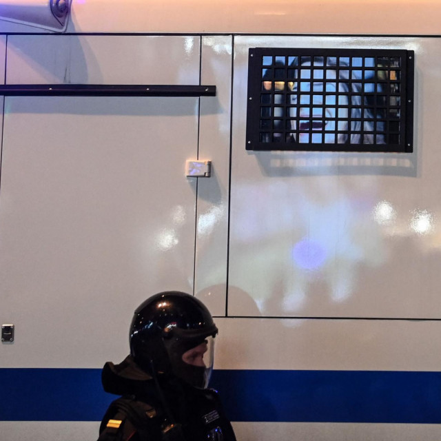 A Russian riot police officer patrols near a police bus with an advertising photo reflecting on a window during a rally in support of jailed Kremlin critic Alexei Navalny, in Moscow on April 21, 2021. - Jailed Kremlin critic Alexei Navalny's team called for demonstrations in more than 100 cities, after the opposition figure's doctors said his health was failing following three weeks on hunger strike. (Photo by Kirill KUDRYAVTSEV/AFP)