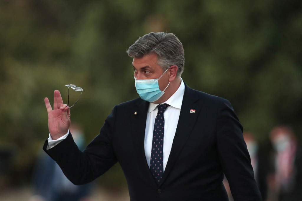 Croatia's Prime Minister Andrej Plenkovic (L) waves as he arrives for an informal dinner event at the Crystal Palace in Porto, on May 7, 2021, within the framework of the Porto Social Summit hosted by the Portuguese presidency of the Council of the European Union. - EU leaders meet to survey the economic wreckage of the Covid pandemic, with high hopes from summit host Portugal that they will swear off austerity and tackle poverty. Twenty-four of the EU's 27 leaders will gather in person in the riverside city of Porto for a summit that will make social issues a priority after two historic economic crises hit Europe over the past decade. (Photo by Luis Vieira/POOL/AFP)