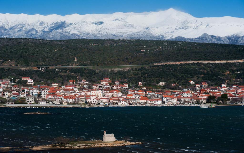 Posedarje, Zadar, 091212.<br /> Nakon sto je jucerasnji dan obiljezio snijeg, sinoc i danas je na Jadranu zapuhala olujna, ponegdje i orkanska bura sa udarima i preko 200km/h.<br /> Na fotografiji: Posedarje; u pozadini Sveto brdo pod snijegom; u prvom planu crkvica sv. Duh.<br />