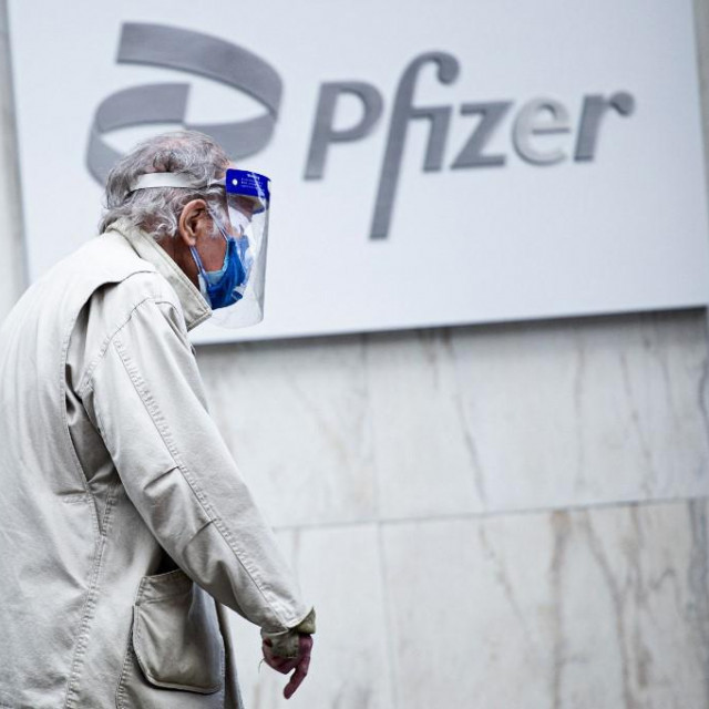 """(FILES) In this file photo taken on March 11, 2021, a man wearing facemask and shield walks past the Pfizer headquarters in New York one year after the pandemic was officially declared. - The Pfizer and Moderna Covid vaccines should remain highly effective against two coronavirus variants first identified in India, according to new research carried out by US scientists. The lab-based study was carried out by the NYU Grossman School of Medicine and NYU Langone Center and is considered preliminary because it has not yet been published in a peer-reviewed journal.<br /> """"What we found is that the vaccine's antibodies are a little bit weaker against the variants, but not enough that we think it would have much of an effect on the protective ability of the vaccines,"""" senior author Nathaniel """"Ned"""" Landau told AFP on on May17, 2021. (Photo by Kena Betancur/AFP)"""