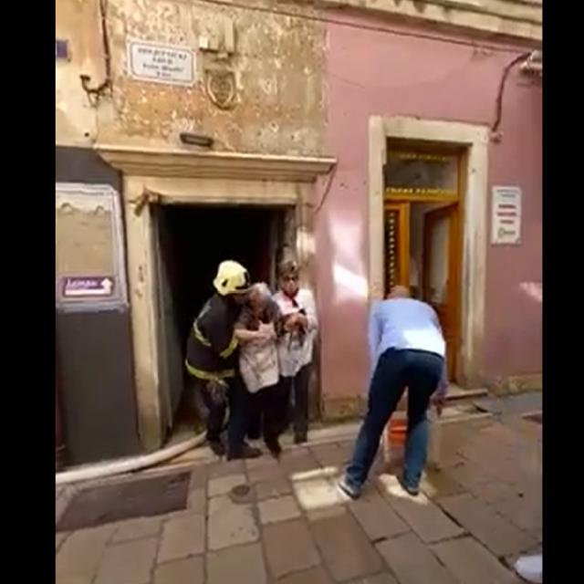 Vatrogasac pomaže starici da izađe iz požarom zahvaćene zgrade
