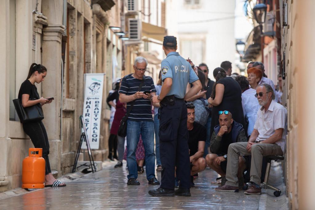 Željko Maričić (krajnje desno) sjedi ispred ulaza u svoj izgorjeli foto atelje u ulici Mihovila Klaića