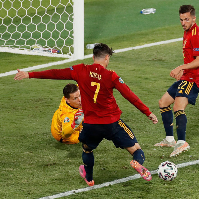 Poland's goalkeeper Wojciech Szczesny (L) tries to stop a shot from Spain's forward Alvaro Morata (C) during the UEFA EURO 2020 Group E football match between Spain and Poland at La Cartuja Stadium in Seville, Spain, on June 19, 2021. (Photo by Jose Manuel Vidal/POOL/AFP)