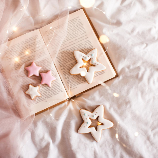Open book with gingerbreads with glowing lights closeup in bed. Winter holiday season. Good morning. Xmas.