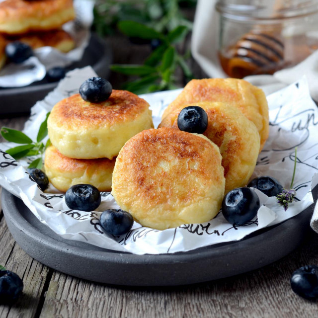 cheese pancakes with blueberries, blackberries and honey on a wooden table