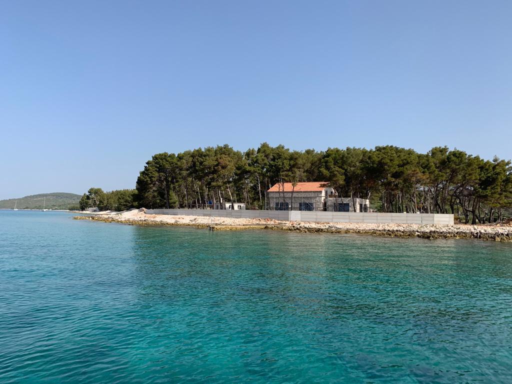 Zemljište s pogledom na otoke Svetu Fumiju i Šoltu omeđeno je zidom podignutim na (javnom) pomorskom dobru