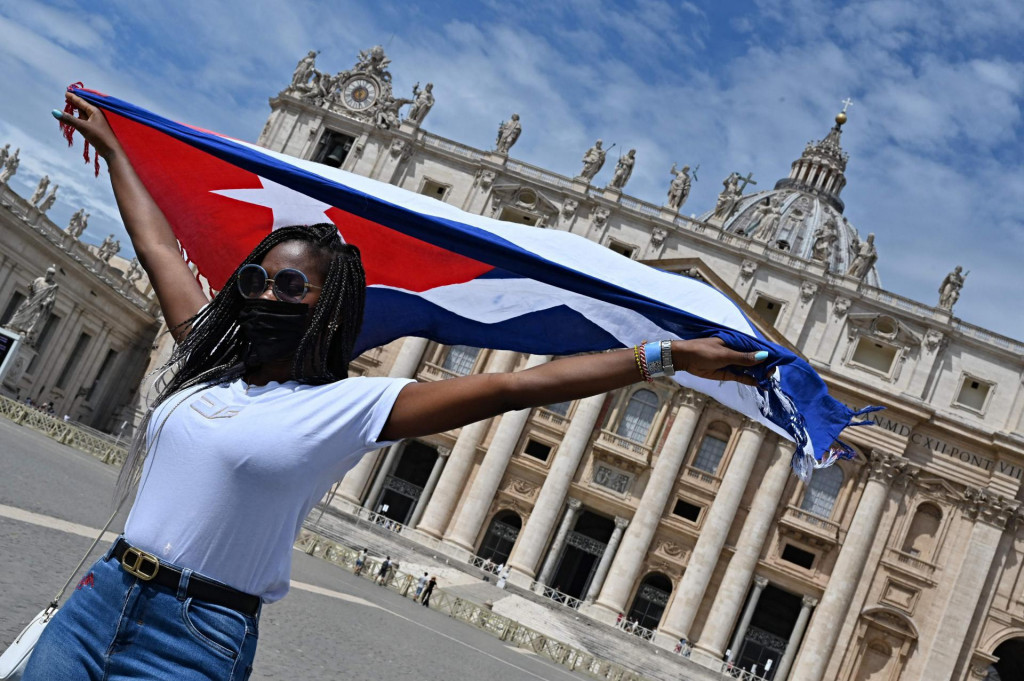 A member of the Cuban community in Italy poses with the national flag for photographers prior to Pope Francis delivering the Sunday Angelus prayer from the window of his study overlooking St. Peter' Square at the Vatican on July 18, 2021. - Pope Francis on July 14, 2021, left the Rome hospital where the head of the world's 1.2 billion Catholics had undergone an operation on his colon on July 4. The 84-year old was whisked away from the Gemelli University Hospital in a car with tinted windows and was later spotted returning to his home within the Vatican's walls. (Photo by Andreas SOLARO/AFP)