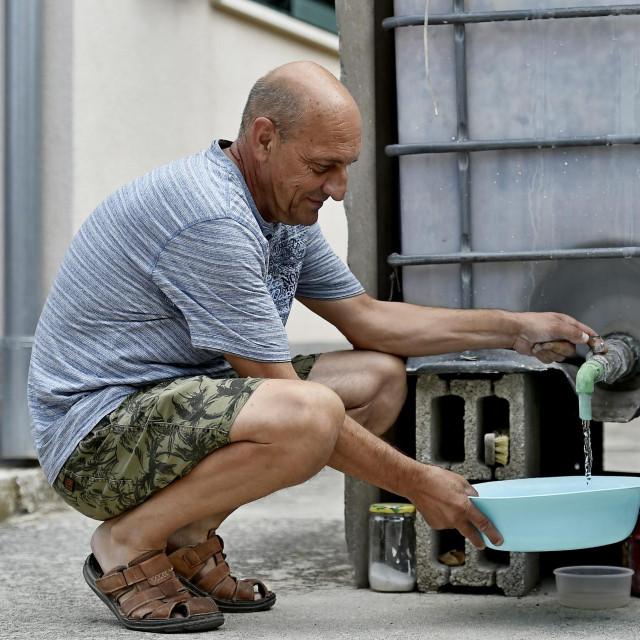 Nikša Vukman iz Okruga Donjeg pored svog spremnika vode