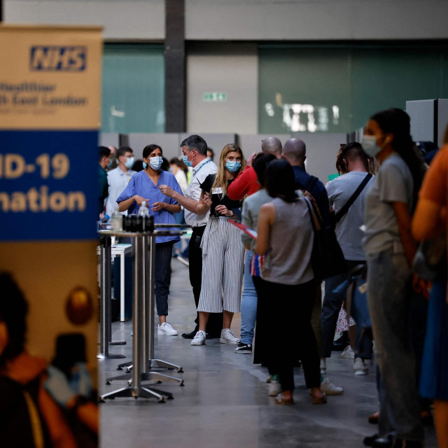 Members of the public queue to receive the Pfizer-BioNTech Covid-19 vaccine in the Turbine Hall at a temporary Covid-19 vaccine centre at the Tate Modern in central London on July 16, 2021. (Photo by Tolga Akmen/AFP)