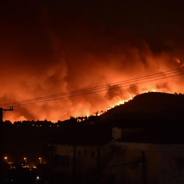 This picture taken on August 5, 2021 shows flames rising from a fire spreading around Kapandriti, on the outskirts of Athens. - Firefighters were battling a series of raging blazes in sweltering heat on August 5, 2021, in western and eastern Greece, and near Athens where a fire that had been coming under control regained strength. (Photo by Louisa GOULIAMAKI/AFP)