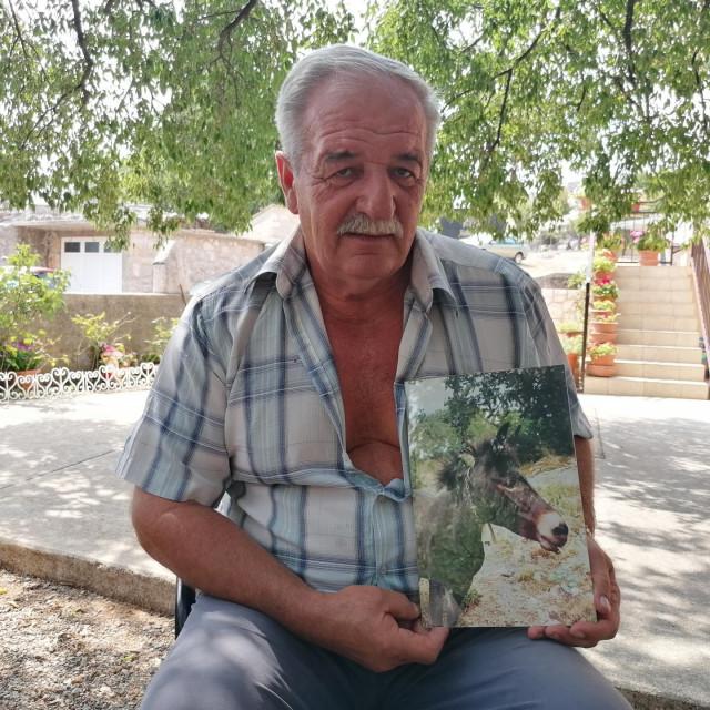 Nediljko Matak pokazuje uokvirenu fotografiju svoje mazge Gare