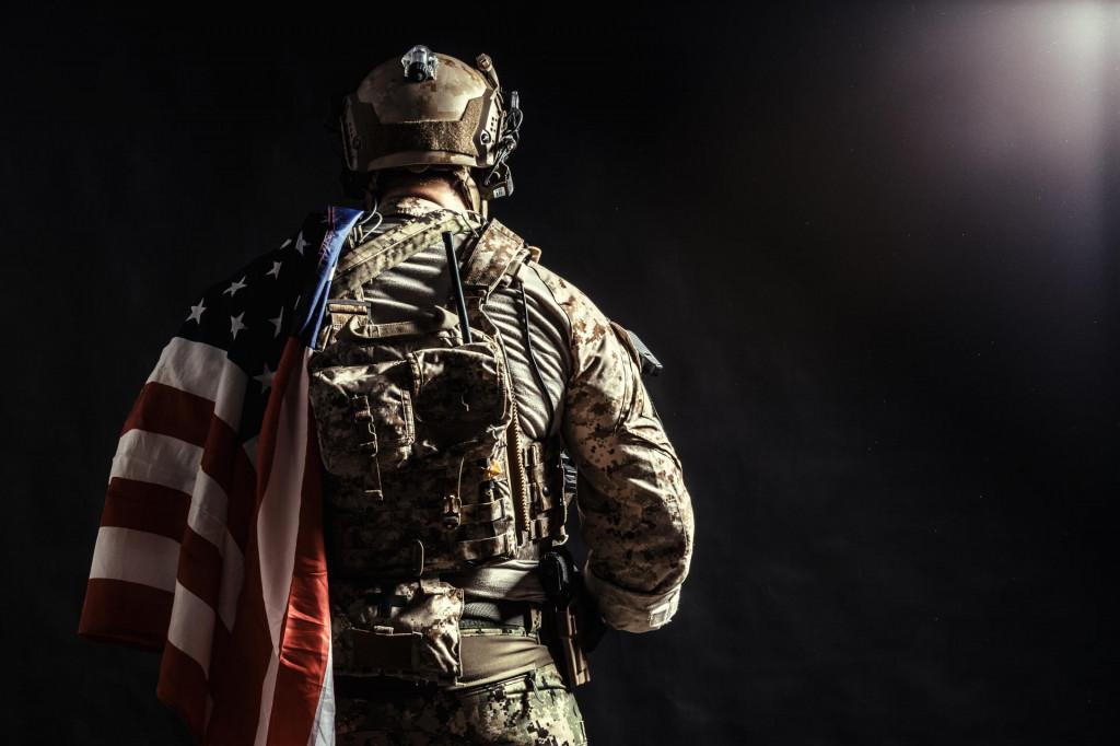 Soldier holding machine gun with national flag