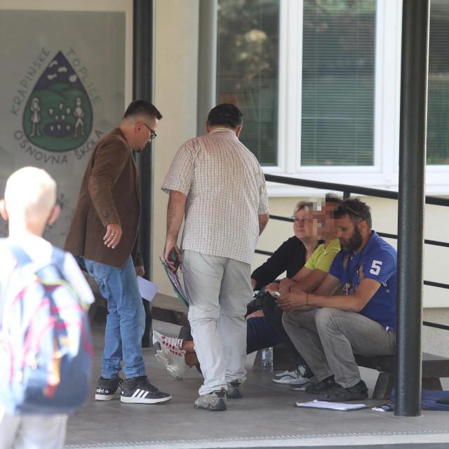 Otac Kristijan Gaćina i majka sjede ispred škole sa svojim sinom, učenikom osmog razreda, kojeg bez maske nisu pustili u školu<br />