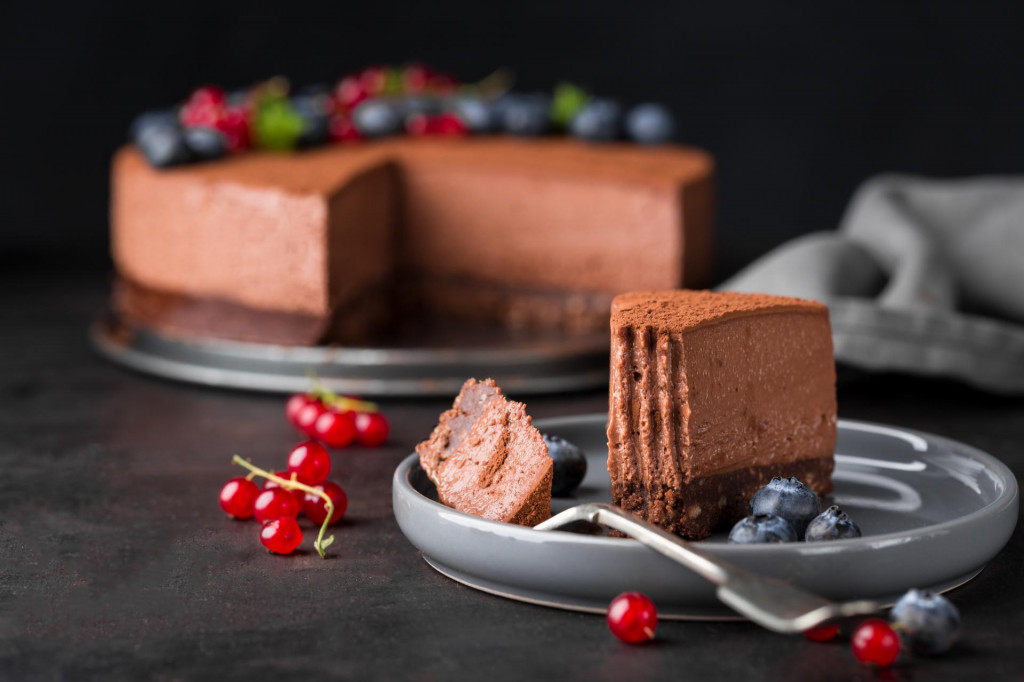 Piece of chocolate cheesecake with berries on dark background, close up