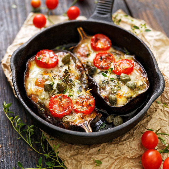 Baked eggplant stuffed with vegetables and mozzarella cheese with addition aromatic herbs. Delicious vegetarian dish