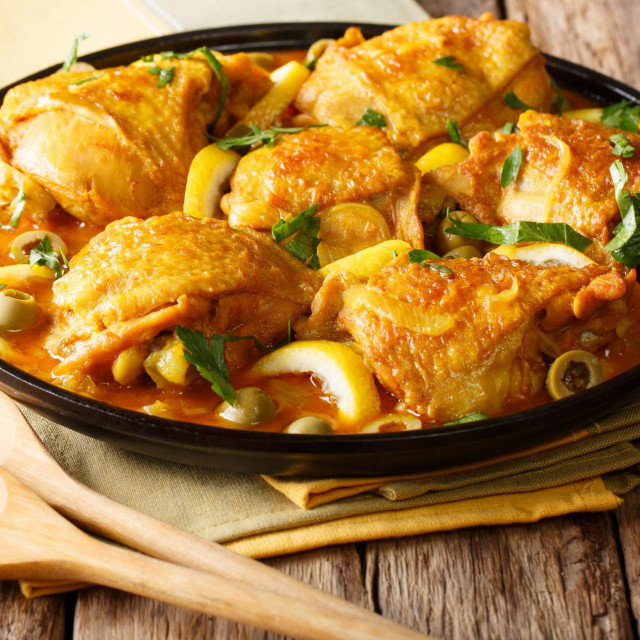 Arabian food: braised chicken with lemons, onions, spices and green olives close-up on a plate on a table. horizontal