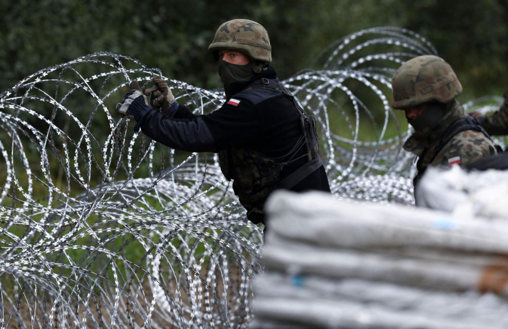 Polish soldiers construct a barbed wire fence on the border with Belarus in Zubrzyca Wielka near Bialystok, eastern Poland on August 26, 2021. - The Polish Ministry of Defence has announced the building of a one hundred kilometer long, two and a half meter high fence along it's border with Belarus after a significant increase in refugee crossings. (Photo by Jaap Arriens/AFP)