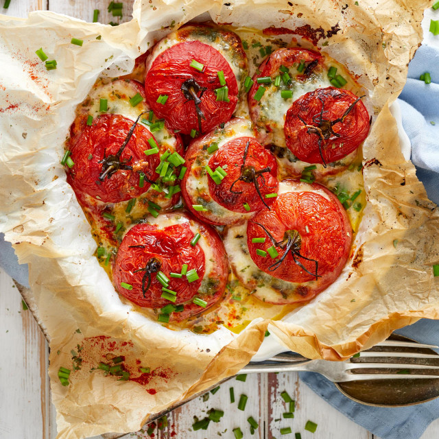 Oven baked tomatoes stuffed with spinach, mozzarella cheese and fresh chive, top view